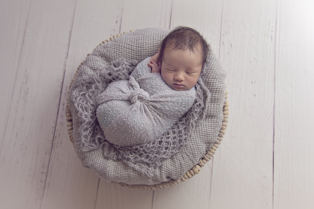 Tiny Feet Photography newborn baby boy posed in grey basket