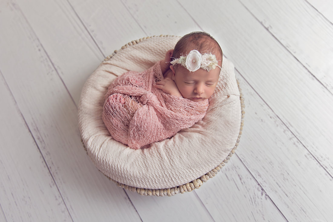 Tiny Feet Photography Newborn baby girl in pink wrap posed in basket