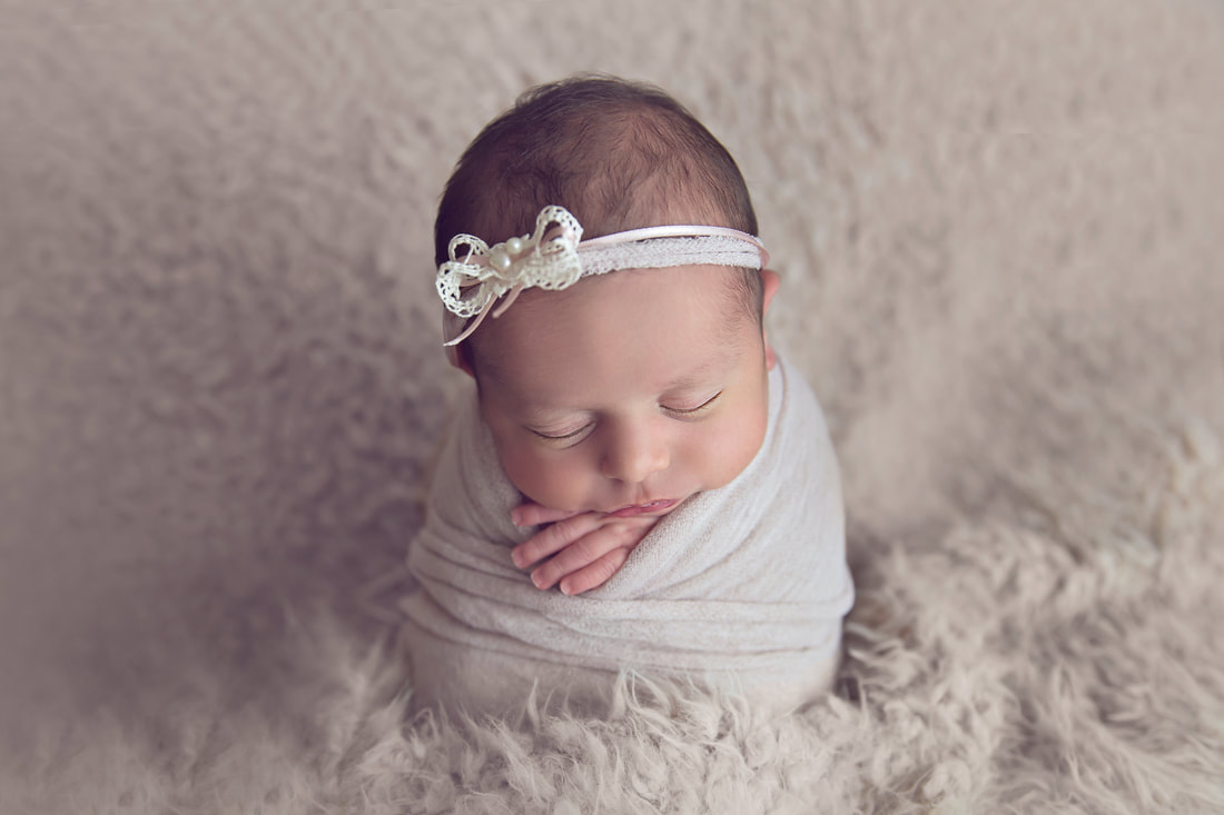 Tiny Feet Photography Newborn baby girl wrapped and posed in potato sack pose on flokati