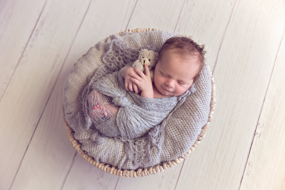 Tiny Feet Photography Newborn baby boy in grey on white basket on white floor boards