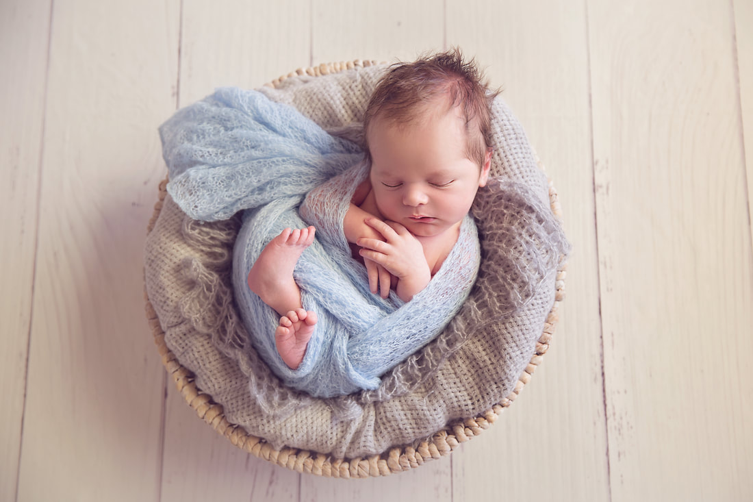 Tiny Feet Photography Newborn baby boy in blue and grey in white basket and white floor boards