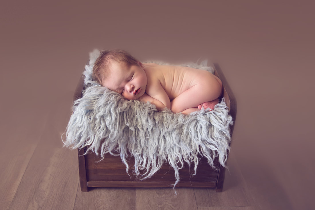 Tiny Feet Photography Newborn baby boy posed in bum up pose on wooden bed