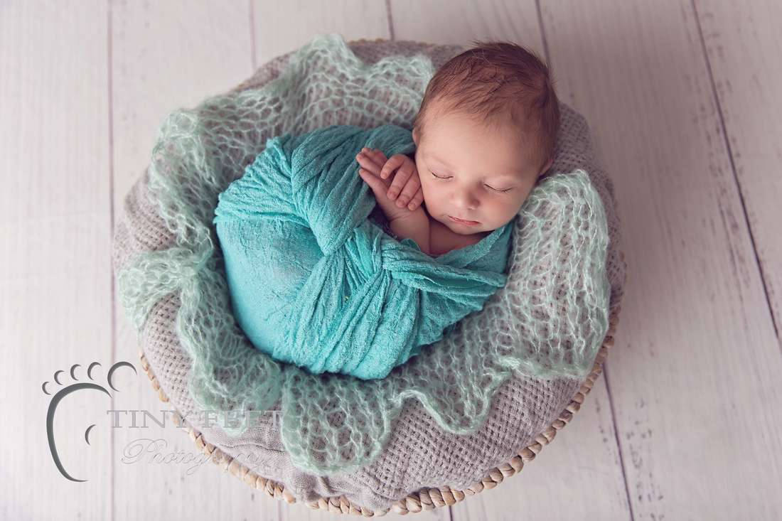 Tiny Feet Photography baby boy wrapped in green wrap in a grey basket