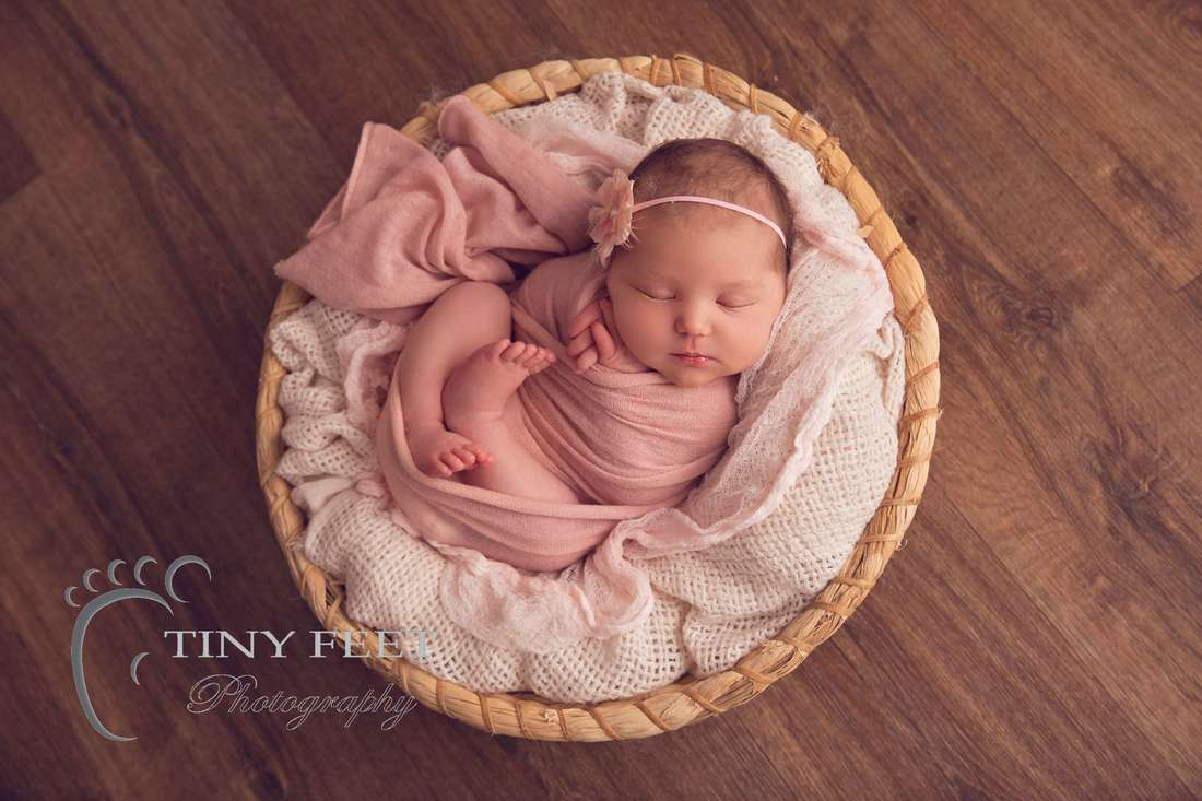 Tiny Feet Photography Perth newborn girl posed in round basket in pink wrap