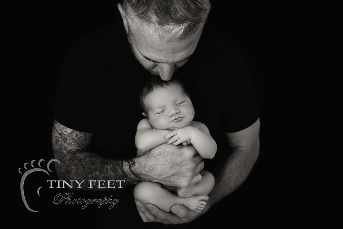 Tiny Feet Photography black and white image of newborn baby boy posed with dad
