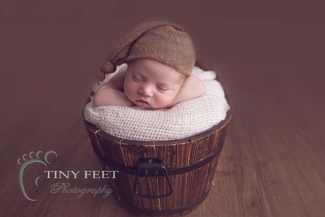 Tiny Feet Photography, newborn baby boy posed chin in hands in bucket