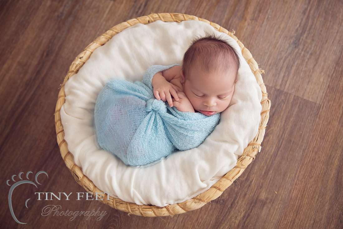 Tiny Feet Photography Newborn boy wrapped in blue and posed in basket
