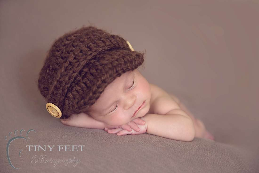 Tiny Feet Photography Newborn boy chin on hand pose on brown blanket