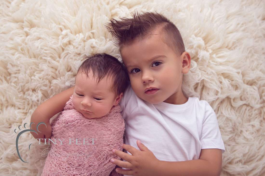 Tiny Feet Photography newborn baby girl wrapped in pink posed with big brother
