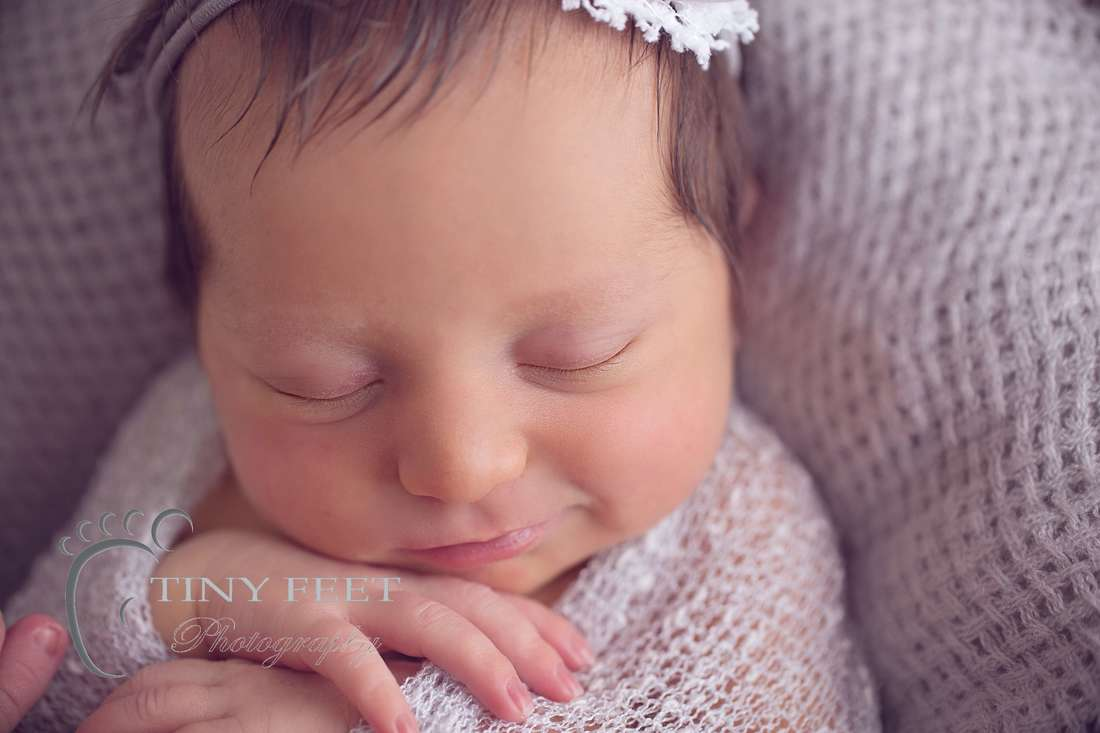Tiny Feet Photography, close up shot of newborn baby girl in grey wrap in a bowl