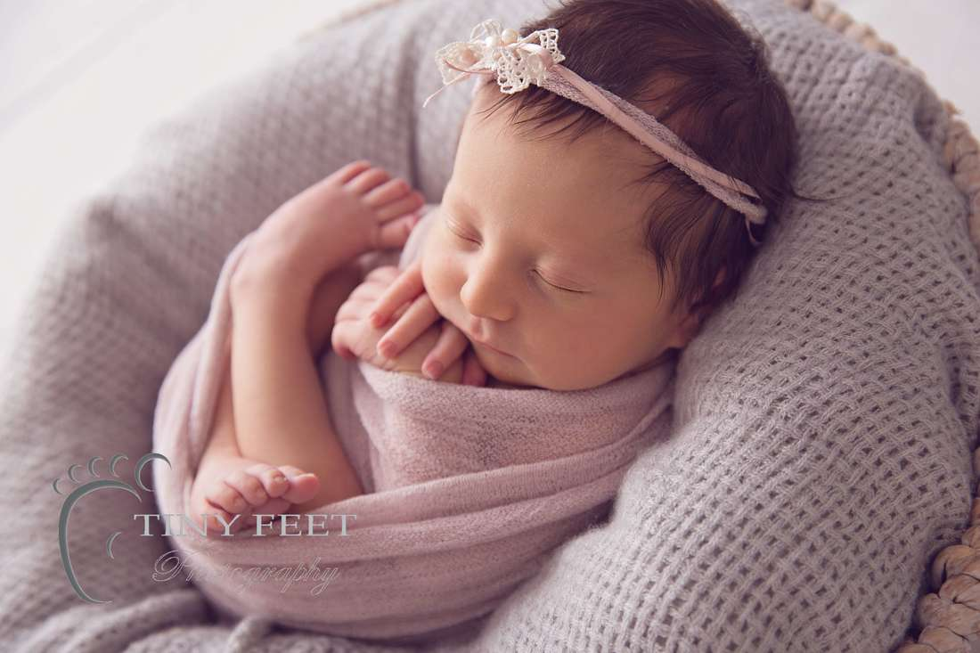 Tiny Feet Photography, newborn baby girl in pink wrap backlit in a bowl