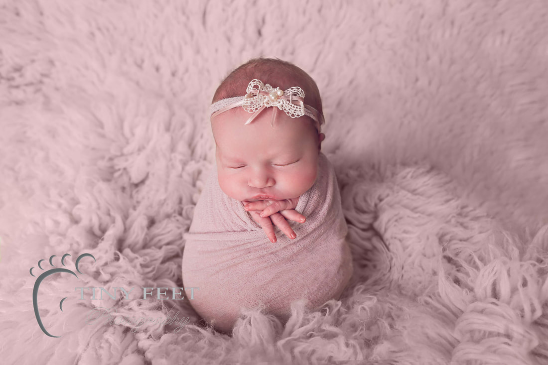 Tiny Feet Photography baby girl posed in pink wrap on flokati in potato sack