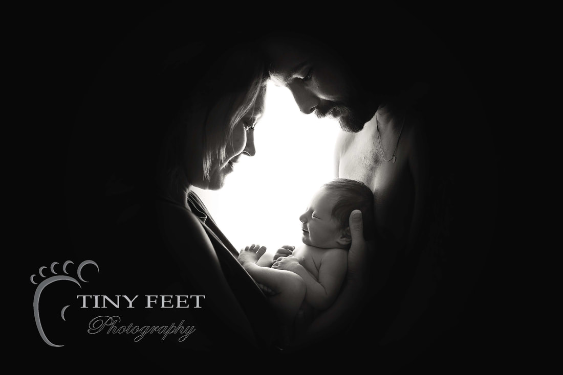 Tiny Feet Photography, newborn baby posed with mum and dad backlit black and white