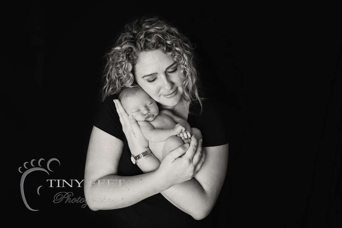 Tiny Feet Photography black and white image of newborn with parents