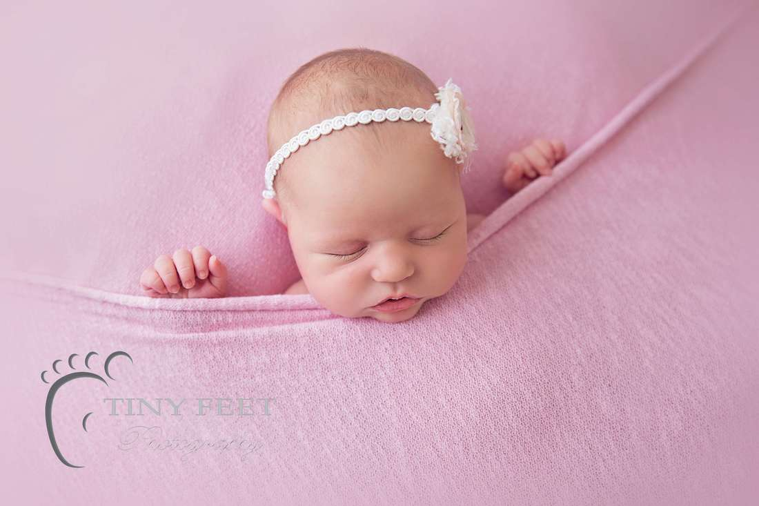 Tiny Feet Photography newborn baby girl tucked in to pink blanket