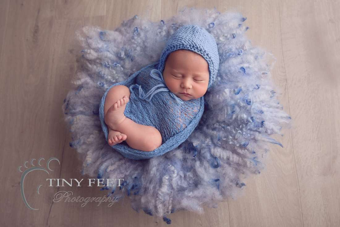 Tiny Feet Photography newborn baby boy in blue wrap with blue curly felt
