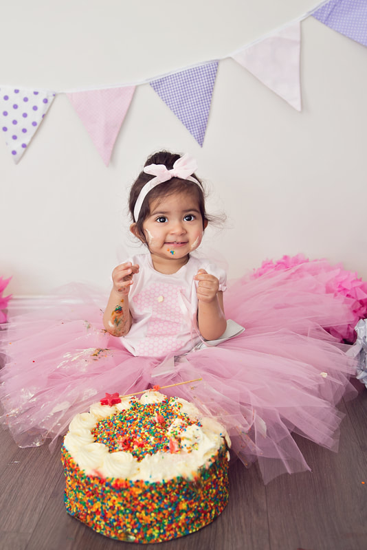 Tiny Feet Photography little girl in pink smashing birthday cake