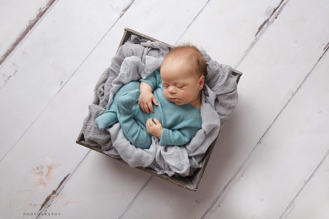 Tiny Feet Photography Newborn baby boy posed in grey box with grey fabric on white wood flooring
