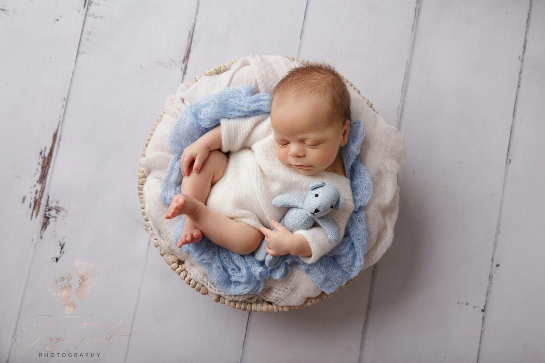 Tiny Feet Photography Newborn baby boy posed in white basket with blue fabric